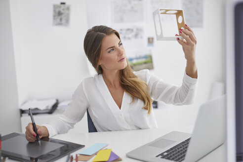 Young woman at desk in office holding model and using graphics tablet - PNEF00147