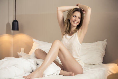 Smiling woman stretching in bed - PNEF00153