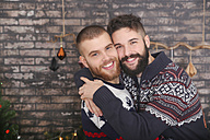 Portrait of happy gay couple embracing at Christmas - RTBF01032