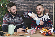 Gay couple preparing hot chocolate with cream and chopped candy canes at Christmas time - RTBF01038