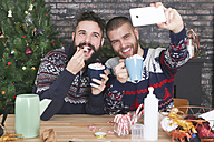 Happy gay couple taking selfie with smartphone at Christmas time at home - RTBF01041