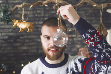 Portrait of man looking through transparent Christmas bauble - RTBF01044