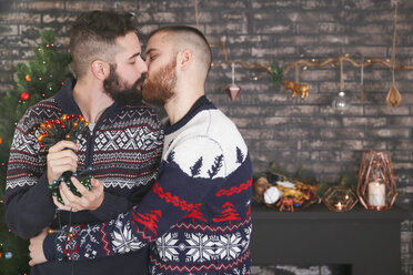 Kissing gay couple with chain of lights at Christmas time at home - RTBF01047