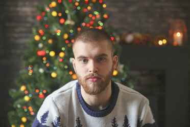 Portrait of serious young man with full beard in front of lighted Christmas tree at home - RTBF01050