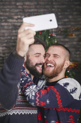 Portrait of laughing gay couple taking selfie with smartphone at Christmas time at home - RTBF01053