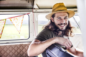 Portrait of happy young man inside a van - FMKF04526