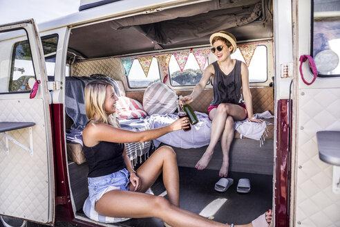 Two happy women inside van clinking bottles - FMKF04529