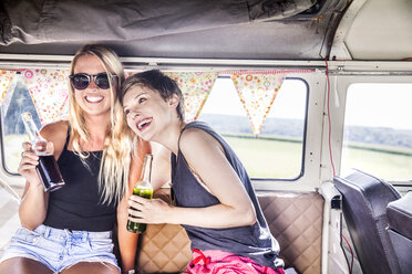 Two happy women inside van with bottles - FMKF04532
