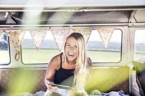 Carefree woman with tablet inside a van - FMKF04535