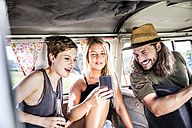 Happy friends inside van looking at smartphone - FMKF04538