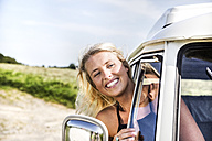 Happy woman looking out of window of a van - FMKF04541