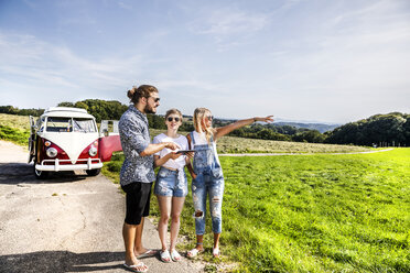 Friends with tablet outside van in rural landscape - FMKF04544