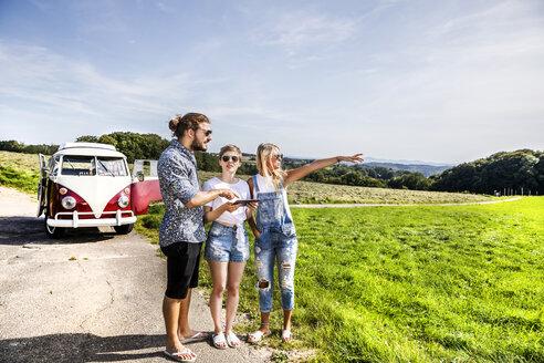 Friends with tablet outside van in rural landscape - FMKF04544