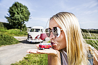 Woman wearing sunglasses kissing van model - FMKF04547