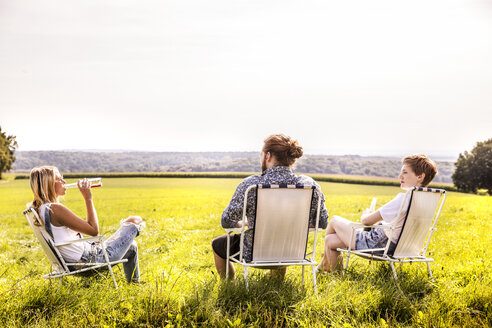Friends sitting on camping chairs in rural landscape - FMKF04550