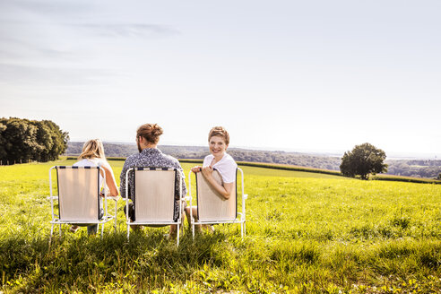 Friends sitting on camping chairs in rural landscape - FMKF04553