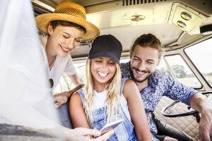 Happy friends inside van looking at smartphone - FMKF04562
