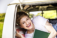 Happy woman with book in a van - FMKF04565