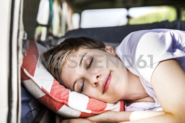 Smiling woman sleeping in a van - FMKF04568
