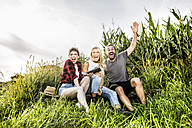 Carefree friends with tablet sitting at a cornfield - FMKF04574