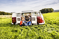 Friends having picnic in a van parked on field in rural landscape - FMKF04580