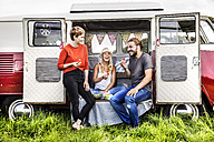 Happy friends having picnic in a van parked on field - FMKF04583
