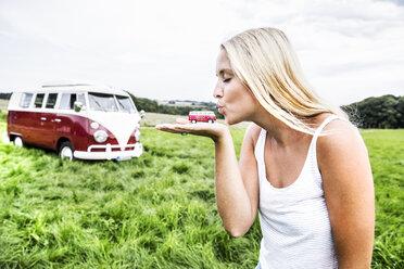 Woman kissing van model next to van in rural landscape - FMKF04592