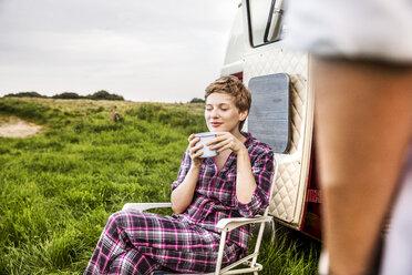 Woman in pyjama enjoying coffee at a van in rural landscape - FMKF04595