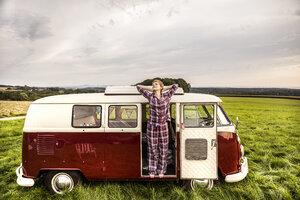 Woman in pyjama stretching in a van in rural landscape - FMKF04598