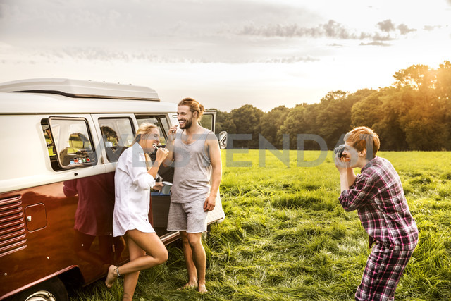 Woman taking picture of friends brushing teeth at a van in rural landscape - FMKF04601