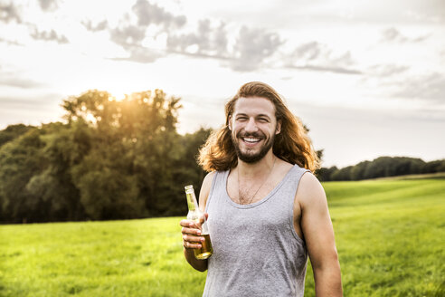 Portait of happy man drinking beer in rural landscape - FMKF04607