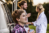 Woman with friends enjoying coffee at a van in rural landscape - FMKF04610