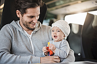 Happy father with baby girl traveling by train - DIGF02873