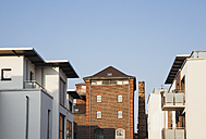 Germany, Cologne, Widdersdorf, modern town houses and an old industrial building at morning sunlight - GWF05281