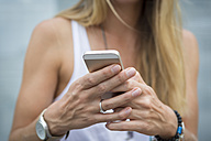 Close-up of woman holding cell phone - JUNF00921