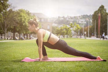 Young woman practicing yoga in a park in the city - JUNF00930