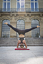 Young woman doing a headstand during a yoga exercise in the city - JUNF00933