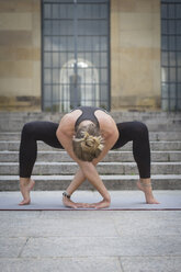 Young woman practicing yoga in the city - JUNF00936