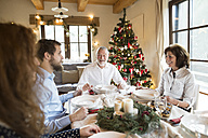Smiling senior man with family at Christmas dinner table - HAPF02179