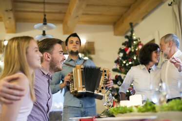 Young man playing accordion for family at Christmas - HAPF02209
