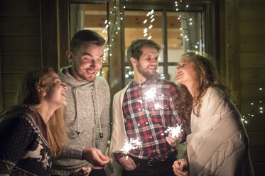 Happy friends holding sparklers outdoors at night - HAPF02221