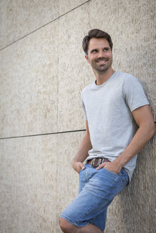 Man leaning against wall, smiling - JUNF00938