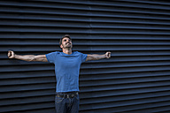 Man standing in front of roller shutter, looking up with arms outstretched - JUNF00953