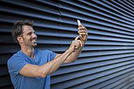 Man standing in front of roller shutter, taking a selfie - JUNF00956