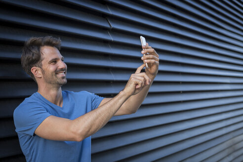 Man standing in front of roller shutter, taking a selfie - JUNF00956