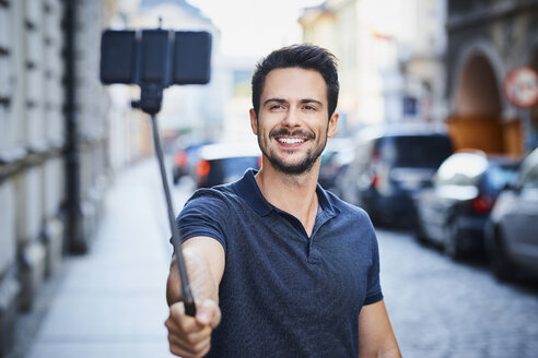 Man taking photo with smartphone mounted on selfie stick - BSZF00073