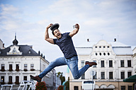 Man jumping and taking selfie holding fedora hat - BSZF00079