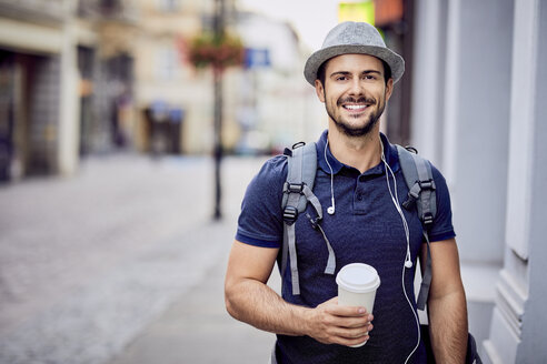Portrait of a traveler with backpack holding coffee - BSZF00082