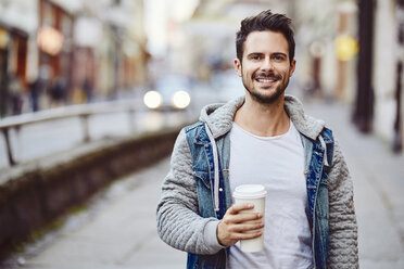 Portrait of smiling man holding coffe with city street in backgorund - BSZF00094