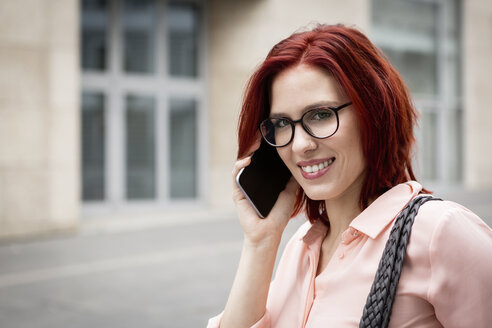 Young businesswoman in the city talking on the phone - JUNF00991